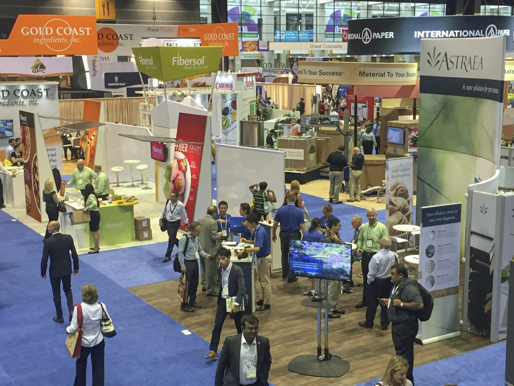 Trade show representatives interact with attendees. B2B trade shows allow businesses to showcase new products to prospects.