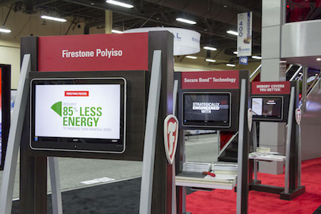 Firestone Building Products' booth activation at IRE 2017, featuring interactive touchscreens with product information.