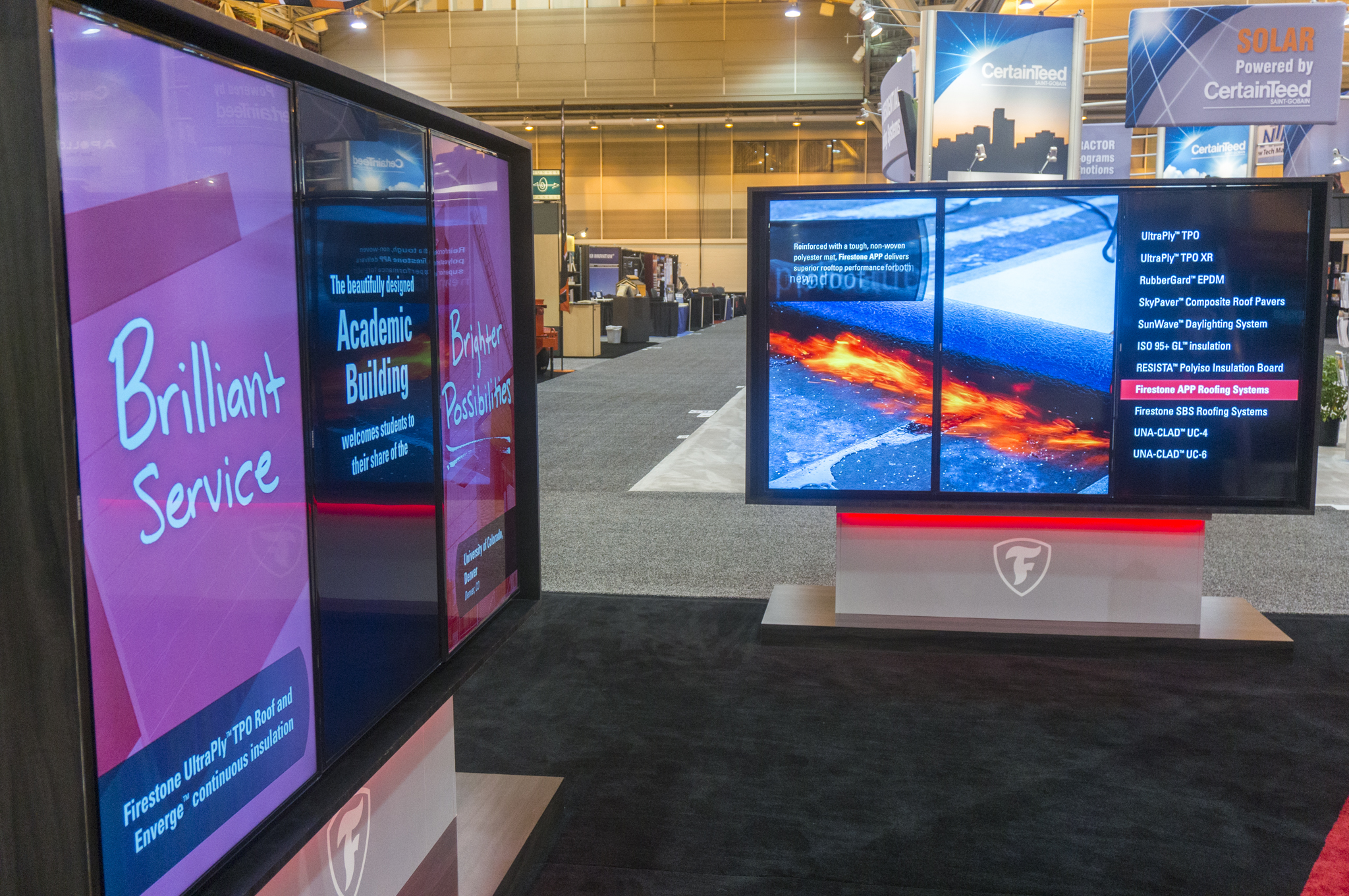 Firestone Building Products' booth activation, featuring large LCD monitors with product information and visuals.
