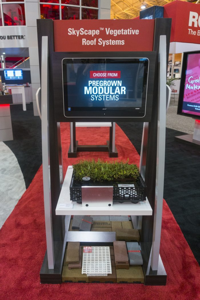 Firestone Building Products' booth activation, featuring interactive touchscreens with product information.