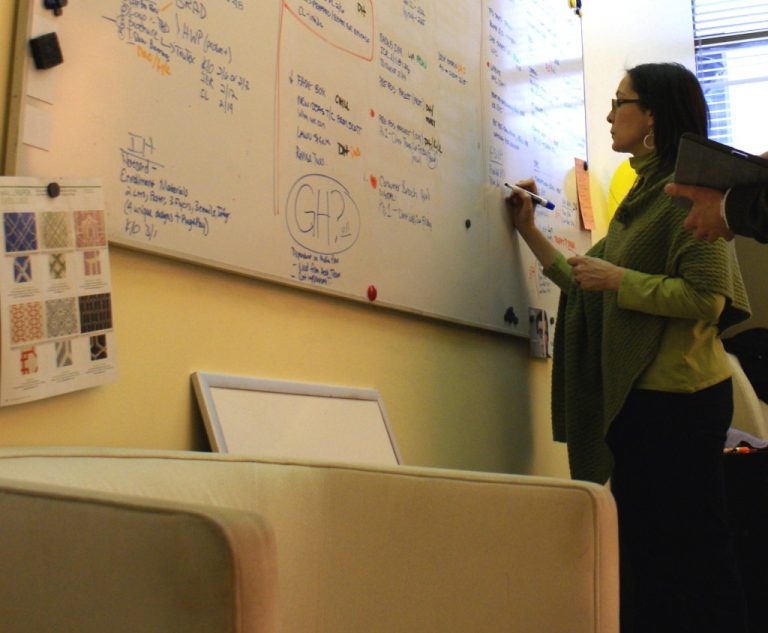 Executive Creative Director and VP Mary Olivieri plans exceptional creative work on a whiteboard at CBD Marketing.
