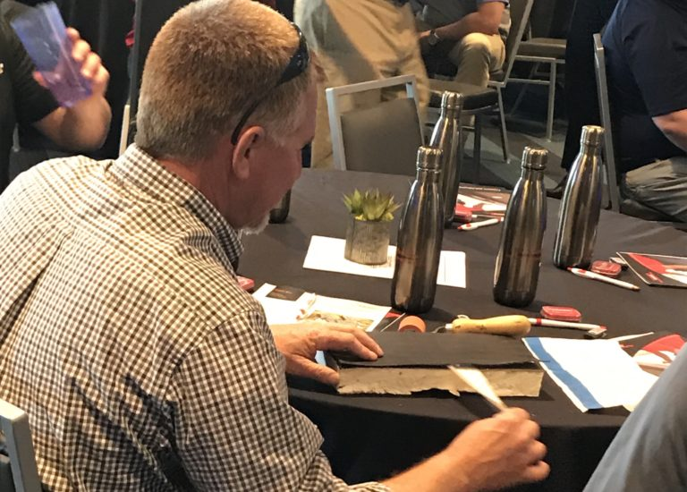 Contractors get hands-on practice with an adhesive product at a demo event.